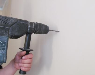 Przewiercamy wiertarką (sugerowane wiertło to 8 mm) otwór na kołki rozporowe a następnie mocujemy do ściany wieszaki rolety