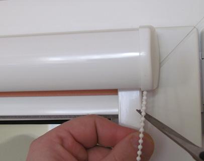 Materiał rolety chowamy do puszki a następnie odcinamy łańcuszek na odpowiednią długość